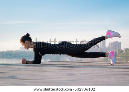 Young pretty woman exercises on pier during sport training