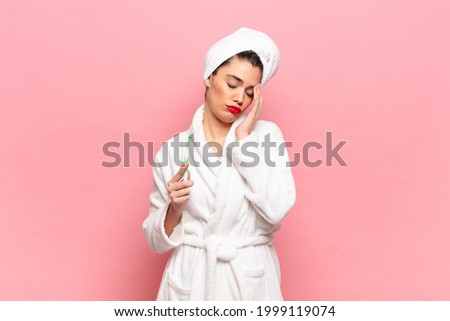 young pretty woman feeling bored, frustrated and sleepy after a tiresome, dull and tedious task, holding face with hand. bathrobe and toothbrush concept Сток-фото ©