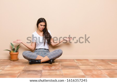 young pretty woman feeling clueless and confused, having no idea, absolutely puzzled with a dumb or foolish look sitting on a floor