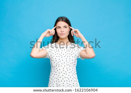 young pretty woman feeling confused or doubting, concentrating on an idea, thinking hard, looking to copy space on side against blue wall