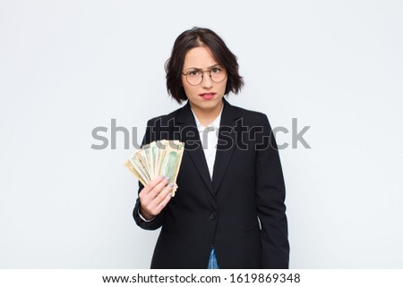 young pretty woman feeling puzzled and confused, with a dumb, stunned expression looking at something unexpected with bills