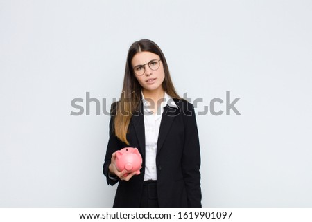 young pretty woman feeling puzzled and confused, with a dumb, stunned expression looking at something unexpected with a piggy bank