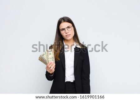 young pretty woman feeling puzzled and confused, with a dumb, stunned expression looking at something unexpected with banknotes