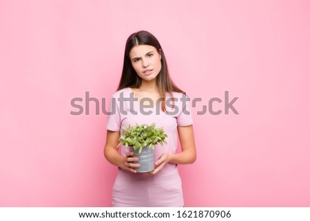 young pretty woman feeling puzzled and confused, with a dumb, stunned expression looking at something unexpected with a plant