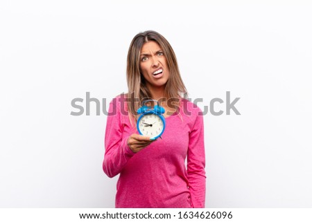 young pretty woman feeling puzzled and confused, with a dumb, stunned expression looking at something unexpected holding an alarm clock.