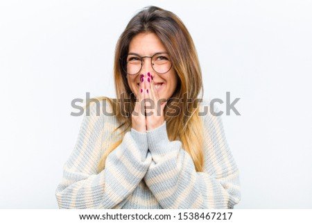 young pretty woman happy and excited, surprised and amazed covering mouth with hands, giggling with a cute expression against white background ストックフォト ©