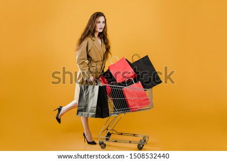 young pretty woman has pushcart with colorful shopping bags and signal tape isolated over yellow