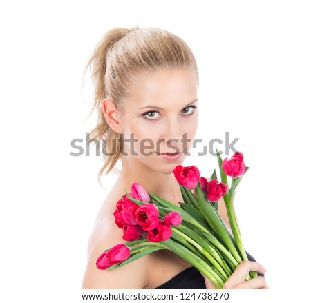 Young pretty woman holding a bunch of red tulips bouquet of flowers smiling on white background