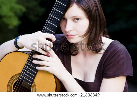 Young pretty woman holding her classic guitar.