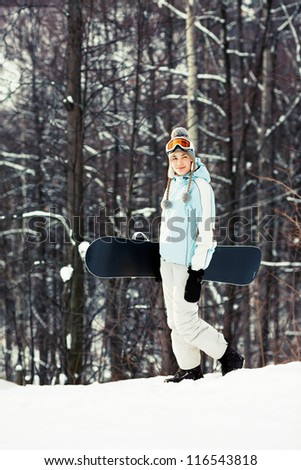 Young pretty woman holding her snowboard and walking on ski slope in sunlight, wood on background, side view, copy space