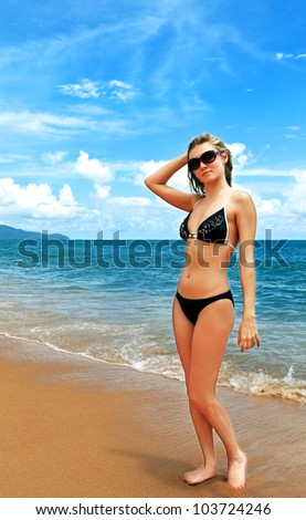 Young pretty woman in bikini and glasses at the beach