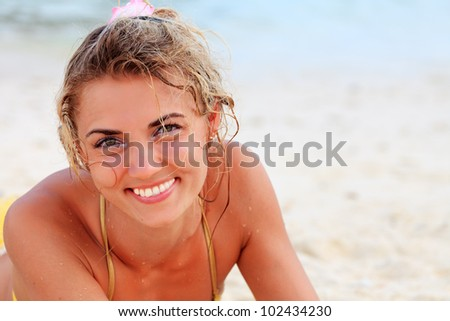 Young pretty woman in bikini at the beach