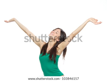 Young pretty woman in green top with arms open feeling freedom and happiness isolated on a white background