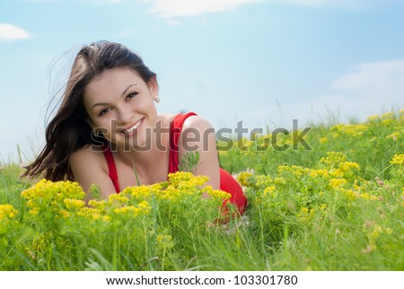 Young pretty woman in red dress lying on green grass