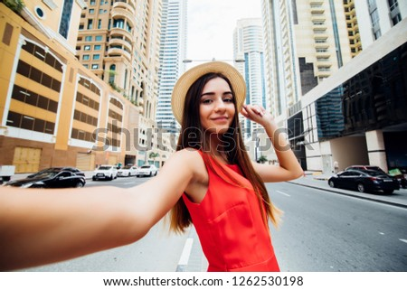 Young pretty woman in red dress take selfie photo in front of skycrapers of modern arhitecture city.