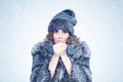 Young pretty woman in silver fox fur coat, hat and scarf, warms her hands, snow background