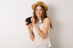young pretty woman in summer vacation style outfit holding vintage photo camera on white background isolated in straw hat, fashion trend, candid smiling natural look, traveling photographer, hobby