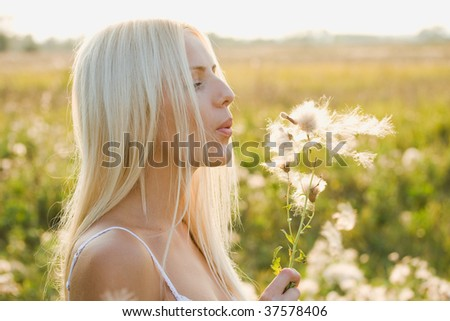 Young pretty woman is blowing to dandelion