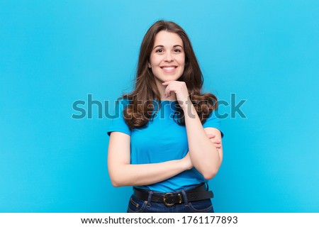 young pretty woman looking happy and smiling with hand on chin, wondering or asking a question, comparing options against blue wall