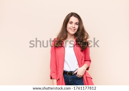 young pretty woman looking proud, confident, cool, cheeky and arrogant, smiling, feeling successful against beige background Foto d'archivio ©