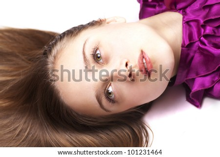 Young pretty woman lying on the floor, close up, looking up, in pink dress