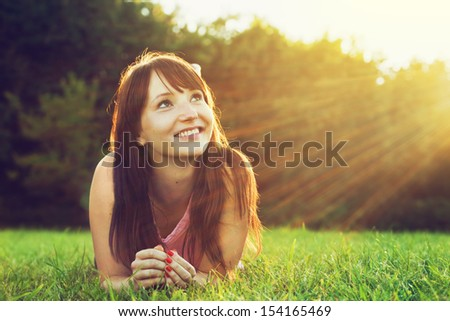 Young pretty woman lying on the grass at summer sunset. Natural happiness, fun and harmony.