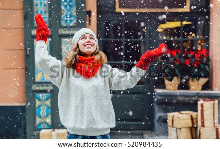 Young pretty woman near the shop with gifts enjoying winter and  looking up on falling snow.\ Girl dressed  in warm white hat, red scarf and mittens.\ Happy holiday  and freedom concept.