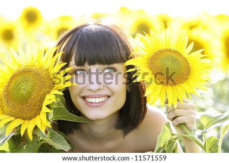 Young pretty woman on a sunflowers background