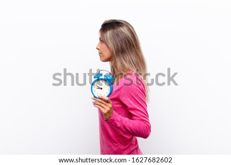 young pretty woman on profile view looking to copy space ahead, thinking, imagining or daydreaming holding an alarm clock.