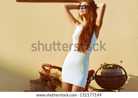 Young pretty woman outdoor fashion portrait. Beautiful girl in sunglasses enjoying the sun on the street