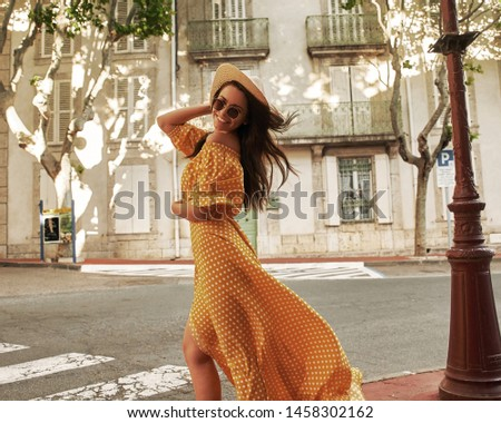 Young pretty woman outdoor portrait. Stylish girl in yellow polka dot dress, sunglasses and thatch hat walking in small european town on a summer day. Vacation and travel concept