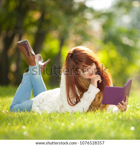 Young pretty woman read electronic book in the park. Beauty nature scene with colorful spring background. Outdoor lifestyle. Happy smiling woman relax with tablet on green grass #1076528357
