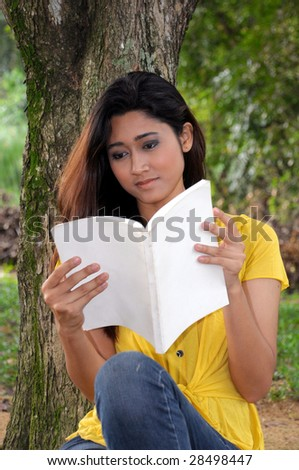 young pretty woman reading a book under a tree