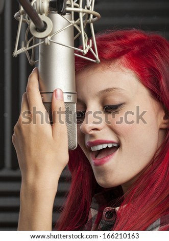 young pretty woman recording on audio studio