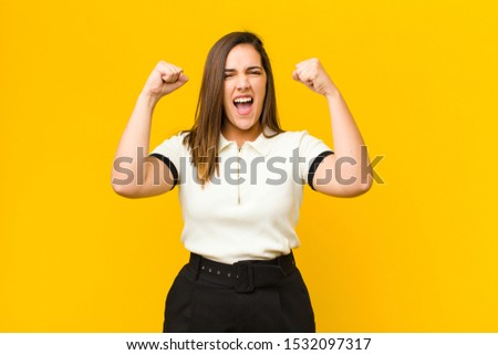 young pretty woman shouting aggressively with an angry expression or with fists clenched celebrating success isolated against orange wall