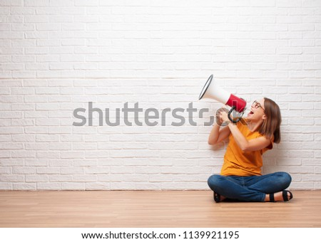 young pretty woman shouting on a megaphone sitting on wooden floor in front a brick wall