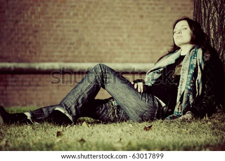 Young pretty woman sitting and resting near tree in park. Old brick wall at background