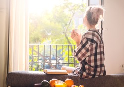 Young pretty woman  sitting at opened window drinking coffee and looking outside enjoys of rest
