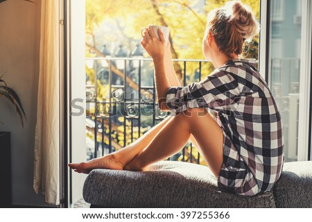 Young pretty woman  sitting at opened window drinking coffee and looking outside enjoys of rest #397255366