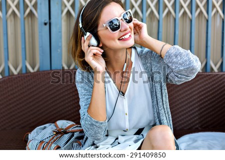 Young pretty woman sitting in the beach wearing stylish casual vintage styled outfit, relaxed and listening music, bright sunny colors, joy, amazing weekends.