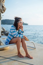 young pretty woman sitting on sun lounger looking at sunset over the sea