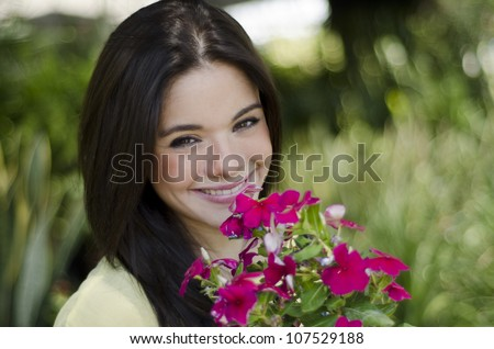 Young pretty woman smiling and holding flowers in a garden