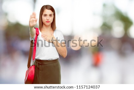 young pretty woman smiling confidently while making a sincere promise or oath, solemnly swearing with one hand over heart.