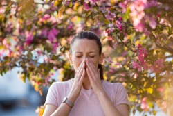 Young pretty woman sneezing in front of blooming tree. Spring allergy concept