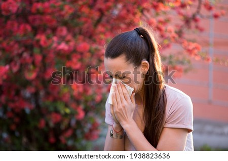Young pretty woman sneezing in front of blooming tree. Spring allergy concept ストックフォト ©