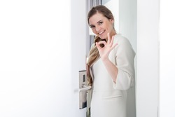 Young pretty woman standing in doorway and making OK sign with her hand