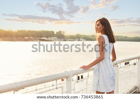 young, pretty woman standing on the riverside bridge in the city