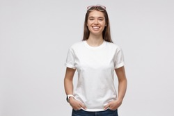 Young pretty woman standing with hands in pockets, wearing blank white t-shirt with copy space for your logo or text, isolated on gray background