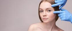 Young pretty woman studio portrait. Cosmetology concept. Esthetic woman face. Skin care dermatology beauty contour. Harmony girl. For cream, lotion horizontal banner. Copyspace
