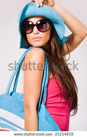 young pretty woman summer portrait in pink dress, sunglasses and hat